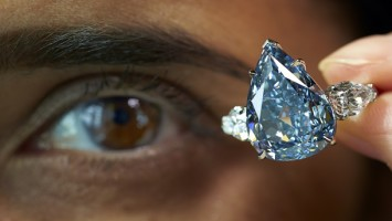"""A staff member poses with """"The Blue"""" diamond during an auction preview for Christie's in Geneva May 9, 2014. The largest flawless vivid blue diamond in the world, weighing 13.22 carats, is expected to reach between CHF 19,000,000 and 23,000,000 (USD 21,000,000 to 25,000,000) when it goes on sale at an upcoming Magnificent Jewels sale in Geneva May 14, 2014. REUTERS/Denis Balibouse (SWITZERLAND - Tags: SOCIETY WEALTH TPX IMAGES OF THE DAY)"""